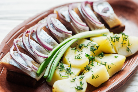 close up of delicious marinated herring with potatoes and onions in earthenware plate Stock fotó - 116556125