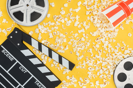 film reels, clapperboard and overturned striped bucket with popcorn isolated on yellow Stockfoto