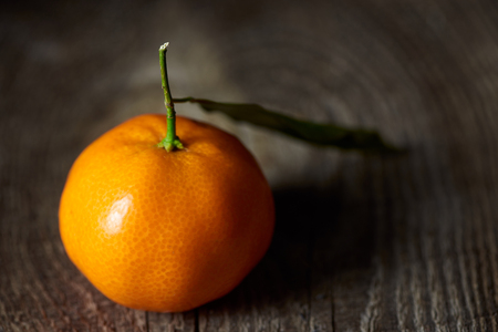selective focus of fresh tangerine with green leaf on wooden table 스톡 콘텐츠