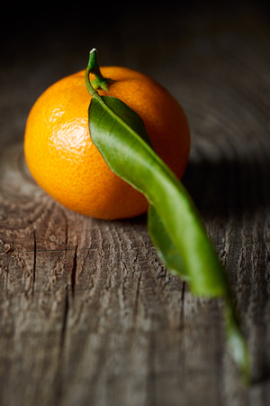 selective focus of juicy tangerine with green leaf on wooden table