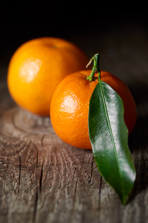 selective focus of green leaf on tasty tangerine on wooden table 스톡 콘텐츠