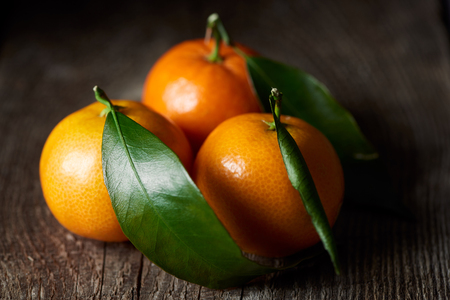 selective focus of organic tasty tangerines with green leaves on wooden table Stockfoto
