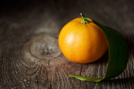 selective focus of organic tasty tangerine on wooden table