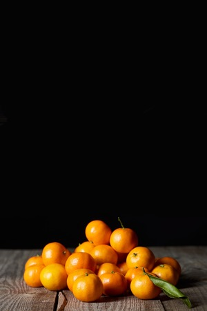 tasty orange tangerines with green leaf on wooden table isolated on black