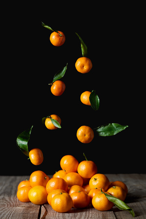 tasty orange tangerines with green leaves falling on wooden table isolated on black