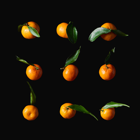 tasty orange tangerines with green leaves isolated on black
