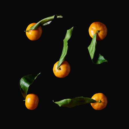 organic tangerines with green leaves isolated on black 스톡 콘텐츠
