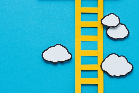 top view of paper ladder with clouds on blue background, setting goals concept