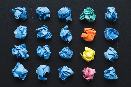 top view of crumpled paper balls with row of colorful ones on black background, think different concept