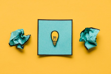 Crumpled paper and note with light bulb drawing on yellow background, ideas concept Stockfoto