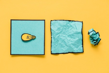 Top view of note with light bulb drawing and crumpled paper on yellow background, ideas concept