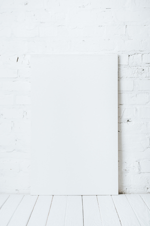 blank placard on white wooden table near brick wall Stock Photo