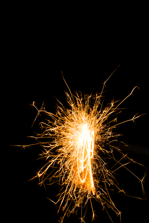 bright burning christmas sparkler on black background Stock Photo