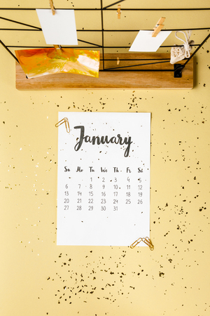 Top view of January calendar with golden confetti and cards with clothespins on beige Archivio Fotografico - 116386082