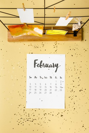 Top view of February calendar with golden confetti and cards with clothespins on beige Archivio Fotografico - 116386081