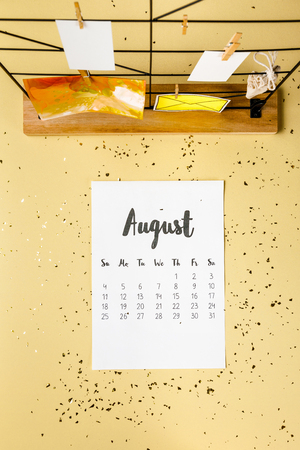Top view of August calendar with golden confetti and cards with clothespins on beige 免版税图像