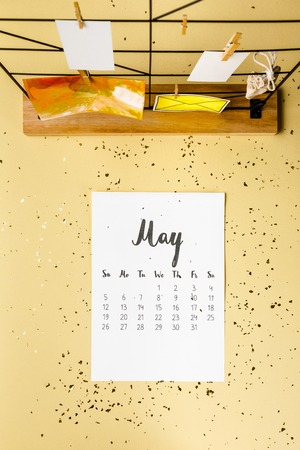 Top view of May calendar with golden confetti and cards with clothespins on beige Archivio Fotografico - 116386088