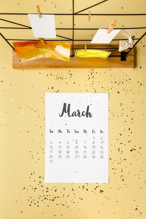 Top view of March calendar with golden confetti and cards with clothespins on beige Archivio Fotografico - 116386087