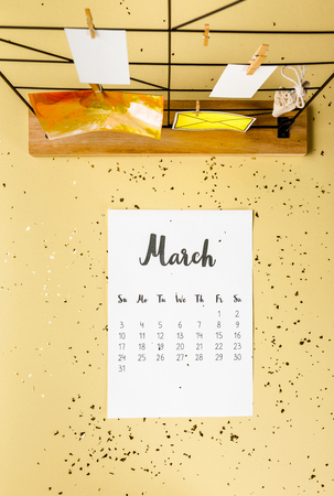 Top view of March calendar with golden confetti and cards with clothespins on beige Archivio Fotografico - 116386089