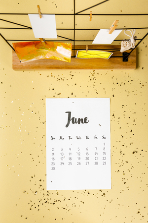 Top view of June calendar with golden confetti and cards with clothespins on beige Archivio Fotografico - 116386090