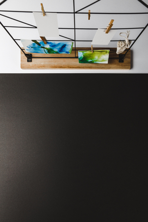 top view of beautiful abstract paintings and blank cards hanging on clothespins, black background Archivio Fotografico - 116386870