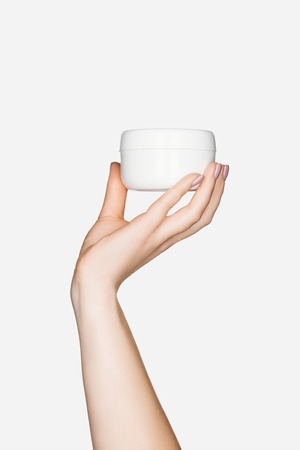 partial view of woman holding hand cream isolated on white