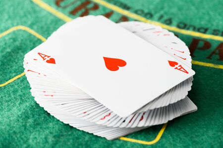 selective focus of playing card with hearts suit on deck at green poker table