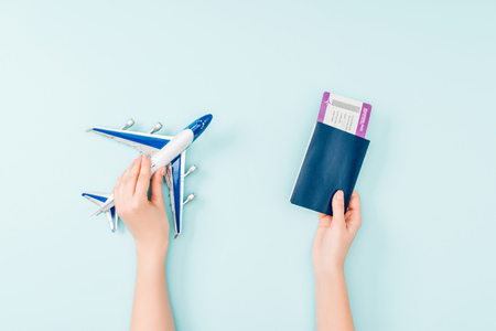 cropped view of woman holding passport, air ticket and toy plane on blue background