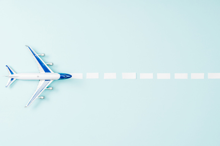 top view of toy plane and dotted line on blue background 版權商用圖片