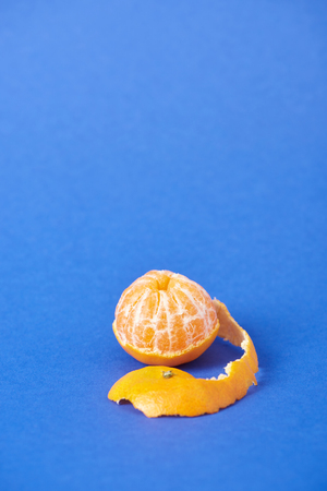 peeled juicy tangerine with zest on blue background Stock fotó