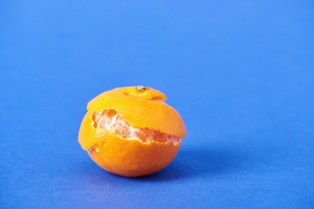 peeled organic tangerine with zest on blue background