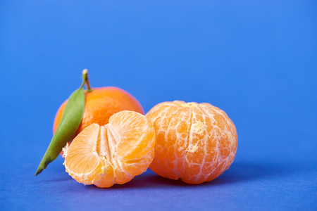 half of peeled tangerine near whole clementines on blue background