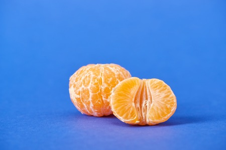 half of peeled tangerine near whole clementine on blue background Stock fotó