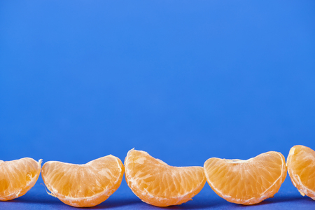 tasty peeled tangerine slices isolated on blue background