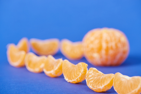 selective focus of tasty peeled tangerine slices on blue background
