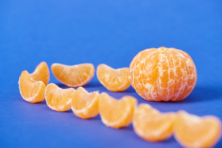 selective focus of tangerine slices near peeled clementine on blue background