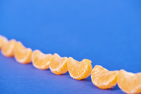 selective focus of peeled tangerine slices on blue background Stock fotó