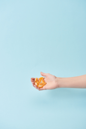 cropped view of woman holding slices of tasty peeled tangerine in hand isolated on blue Stock Photo
