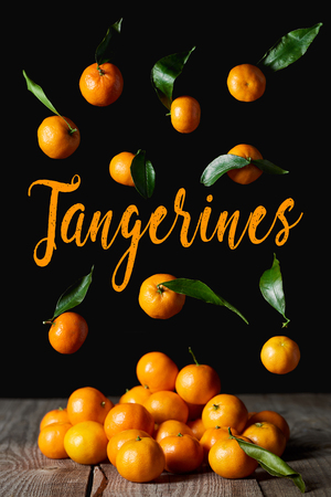 organic tangerines with green leaves isolated on black Stock Photo