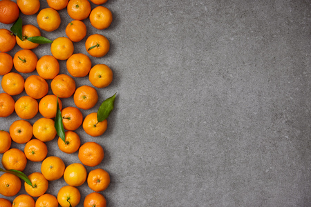 top view of ripe organic clementines with green leaves on grey table