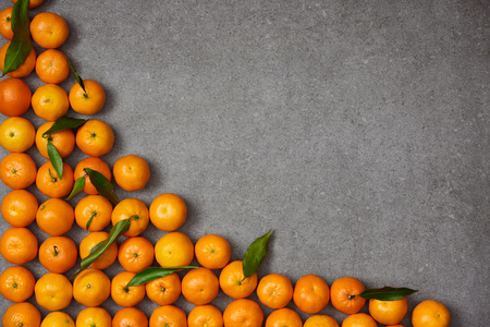 top view of organic tangerines with green leaves on grey table