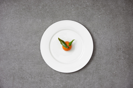top view of sweet organic tangerine with green leaves on white plate