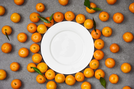 top view of fresh organic tangerines near white plate on grey table Stock Photo