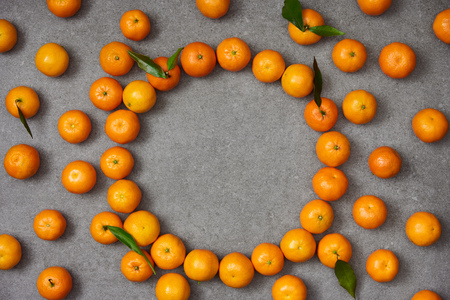 top view of sweet tangerines with green leaves on grey table 写真素材