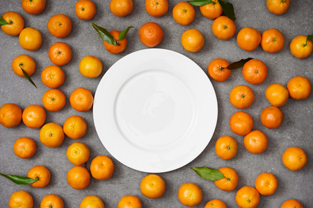top view of sweet organic tangerines near white plate on grey table