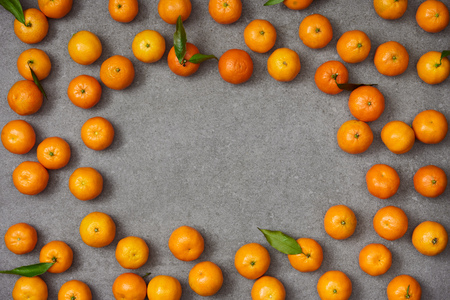 top view of sweet organic tangerines with green leaves on grey table Stock Photo
