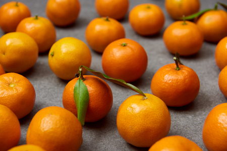 selective focus of organic orange tangerines with green leaves on grey table 스톡 콘텐츠