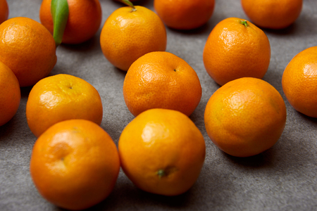 selective focus of organic tangerines on grey table