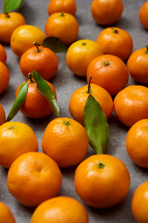 selective focus of sweet tangerines with green leaves on grey table Stock Photo