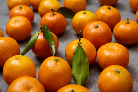 selective focus of orange tangerines with green leaves on grey table